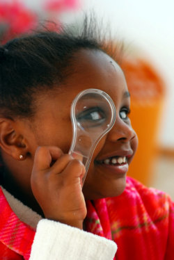 girl looking at a magnifying glass
